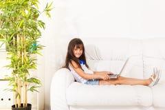 Flicka med bärbara datorn på soffan i profil royaltyfria bilder