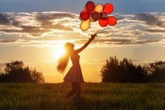 Flicka med ballonger på solnedgången Arkivbild