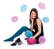 Flicka med ballonger på golvet Arkivfoto
