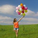 Flicka med ballons royaltyfria bilder