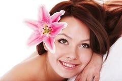 Flicka med blomman i h?r p? massge i brunnsortsalong arkivbild