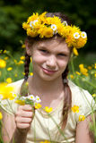 Flicka med blommor i hennes hår på en äng Arkivfoton
