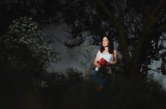 Flicka med blommor i skogen Arkivfoto