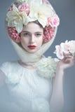 Flicka med blommor på hennes huvud i en klänning i den ryska stilen Dimmaeffekt royaltyfria bilder