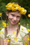 Flicka med blommor på hennes huvud i natur Arkivfoto