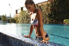 Flicka med blont hår i elegant bikini som kopplar av i simbassäng fotografering för bildbyråer