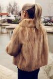 Flicka med blont hår som bär det lyxiga pälslaget Royaltyfri Foto
