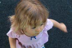 Flicka med blont hår som rotera i rosa klänning på asfalt Sommarsemester, gyckel, glädje, affärsföretagbegrepp Top beskådar arkivbilder