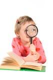 Flicka med boken och förstoringsglaset fotografering för bildbyråer