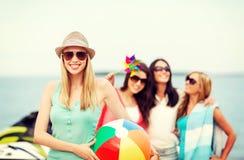 Flicka med bollen och vänner på stranden royaltyfria foton