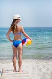 Flicka med bollen på stranden Arkivbild