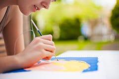 Flicka med borsten som målar en konstbild Arkivfoto