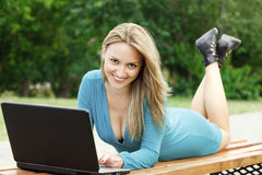 Flicka med bärbar dator som ligger på bänken Arkivbild