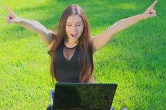 Flicka med bärbar datorjubel Arkivfoto