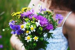 Flicka med buketten av färgrika blommor i sommarfält arkivbilder
