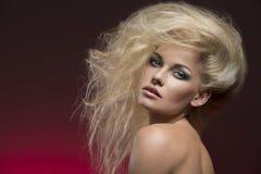Flicka med buskig blond hår-stil Arkivbild