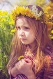 Flicka med chapleten på huvudet i trädgården Royaltyfri Fotografi