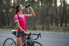 Flicka med cykeldrinkar från flaskan fotografering för bildbyråer