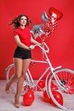 Flicka med cykeln och ballonger Arkivfoto