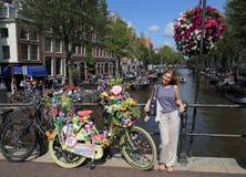 Flicka med cykeln som är full av blommor på den Amsterdam kanalen, Holland Arkivbild