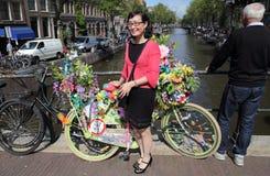 Flicka med cykeln som är full av blommor på den Amsterdam kanalen, Holland Royaltyfri Foto