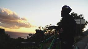 Flicka med cykeln som står på vägen och beundrar havslandskapet på solnedgången stock video