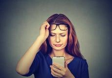 Flicka med dålig vision genom att använda smartphonen royaltyfria foton