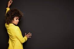 Flicka med den afro frisyren som poserar i gult omslag fotografering för bildbyråer