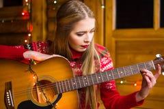 Flicka med den akustiska gitarren i festlig miljö royaltyfri bild