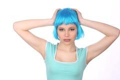 Flicka med den blåa peruken som rymmer hennes huvud close upp Vit bakgrund Royaltyfri Fotografi