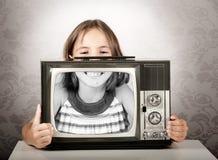 Flicka med den gammala retro televisionen Royaltyfri Foto