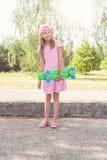 Flicka med den gröna encentmyntskateboarden Royaltyfri Foto