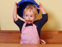 Flicka med den gulliga chokladmunnen som rymmer plastbunken Arkivfoton