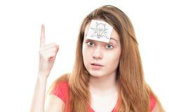 Flicka med den ljusa kulan på papper på henne panna. Arkivbild