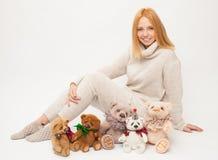 Flicka med den mjuka leksakbjörnen på vit bakgrund Arkivbild