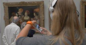 Flicka med den mobila tagande bilden av målning i Louvre stock video