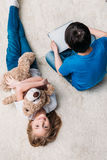Flicka med den nallebjörnen och pojken med den digitala minnestavlan på matta hemma Arkivfoton