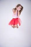 Flicka med den röda kjolbanhoppningen som är lycklig och ler göra den gulliga framsidan royaltyfria foton