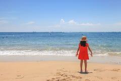 Flicka med den röda klänningen som är främst av havet i bali Arkivfoto