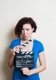 Flicka med den roliga framsida- och filmclapperen på vit bakgrund Royaltyfri Bild