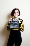 Flicka med den roliga framsida- och filmclapperen på vit bakgrund Royaltyfri Fotografi