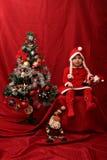 Flicka med den Santa Claus dräkten som spelar med en julgran Royaltyfria Foton