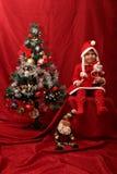 Flicka med den Santa Claus dräkten som spelar med en julgran Arkivfoto