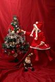 Flicka med den Santa Claus dräkten som spelar med en julgran Arkivfoton