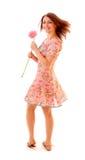 Flicka med den sommarklänningen och blomman Arkivbild