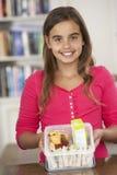 Flicka med den sunda lunchboxen i kök Royaltyfria Bilder