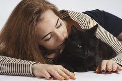 Flicka med den svarta busiga katten på vit nästan isolat royaltyfria bilder