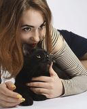 Flicka med den svarta busiga katten på vit nästan isolat arkivfoto