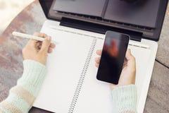 Flicka med den tomma anteckningsboken och en mobiltelefon Arkivbild