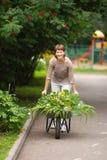 Flicka med den trädgårds- skottkärran Fotografering för Bildbyråer